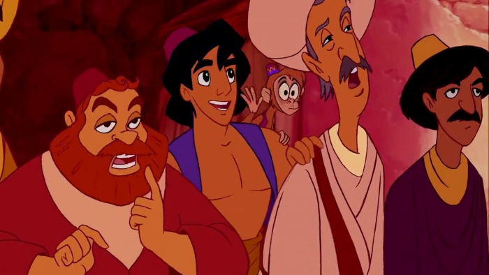 A screen capture from the motion picture Aladdin showing the character of Aladdin and his monkey companion named Abu looking in awe as part of a crowd in a marketplace.