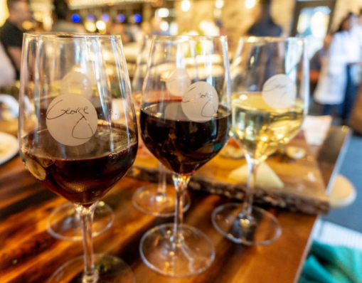 Three wine glasses sit next to each other. They each have a circle shaped logo on them in the center, two contain red wine, and the one on the far end contains white wine. They are on a wooden surface.