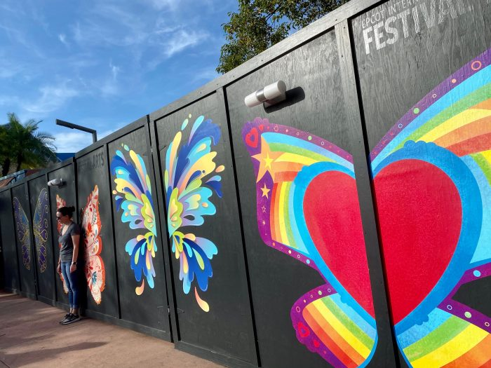 A black wall meant to cover up a construction wall has bright and colorful butterfly wings meant for people to stand in front of so when their picture is taken it looks like they have wings behind them.