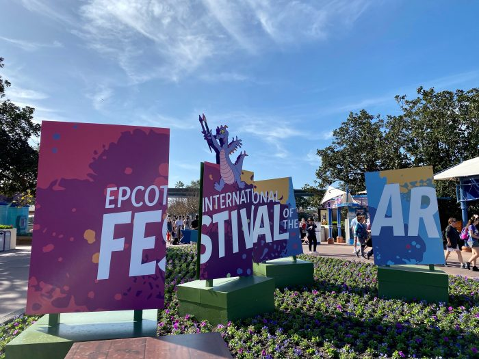 A multiple piece sign with the words Epcot International Festival of the Arts spread out over the multiple pieces. The character, Figment, a friendly purple dragon sits on top of the center piece of the sign.