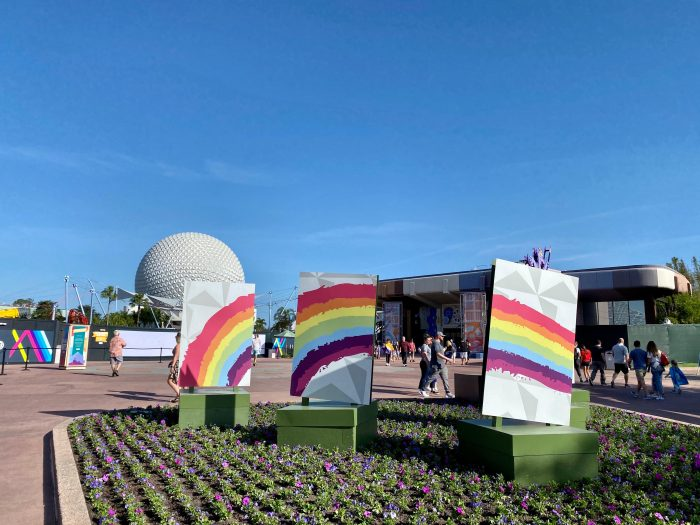 A multiple piece sign has the geographic pattern of Spaceship Earth attraction at Epcot, made of silver triangles. A soft colored rainbow is painted over parts of the pattern. The Spaceship Earth sphere is in the background amid a blue sky.