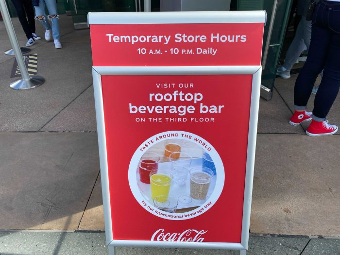 A sign out front of the Coca-Cola Store at Disney Springs indicates the Store Hours of 10 am - 10pm daily, and advertises the rooftop bar on the third floor.