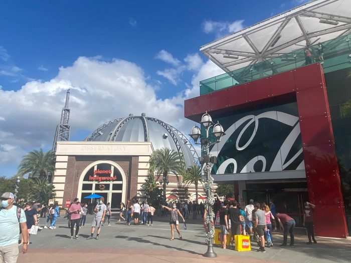 The Coca-Cola Store at Disney Springs stands at the right with Planet Hollywood straight in front, with blue skies and white clouds and moderate crowds of people on the walkway