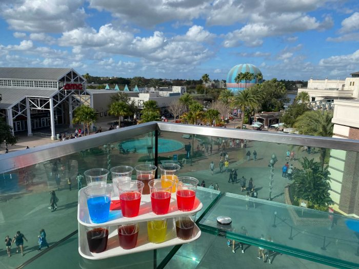 At the rooftop bar of the Coca-Cola Store at Disney Springs. Two trays one stacked on top of the other have 8 clear cups on each tray with various coca-cola beverages from around the world. Some are brightly colored. With a view of Disney Springs below.