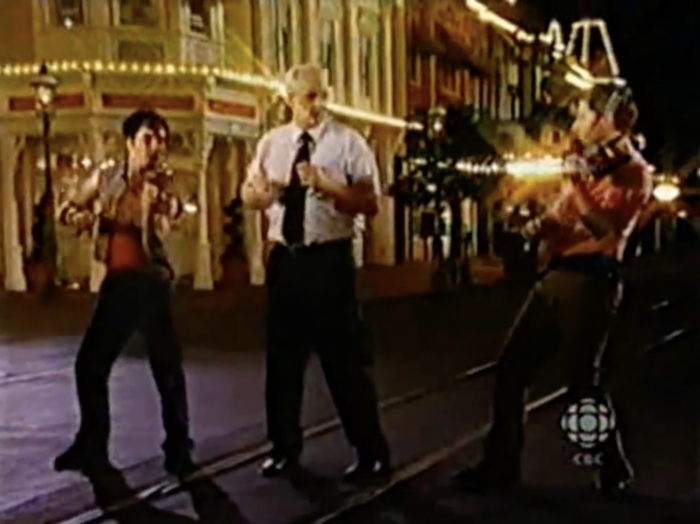 Colin stands on Main Street USA flanked by energetic violinists.