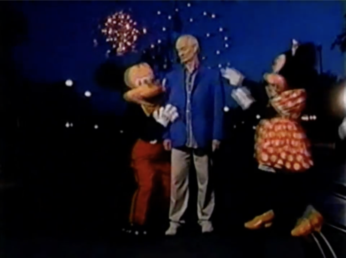 Colin stars with Mickey and Minnie in front of Cinderella's Castle with fireworks in the background.