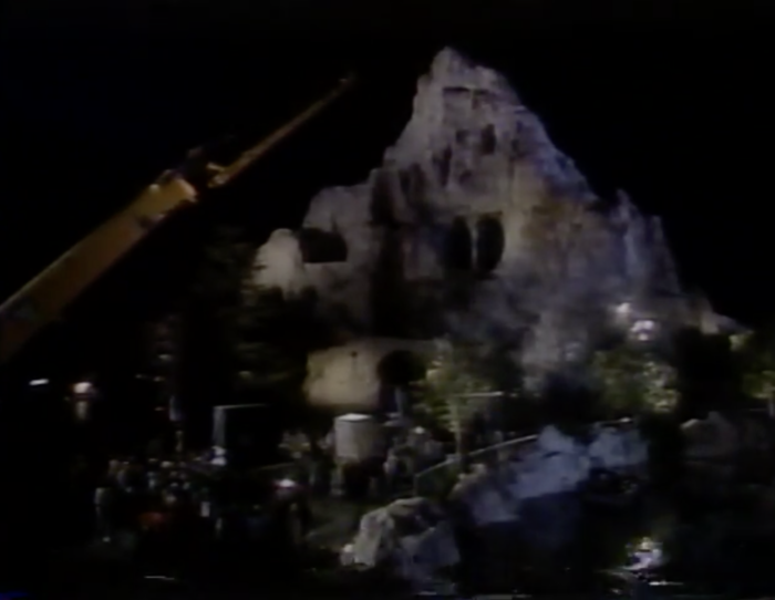 Cage being lifted to go into the Submarine Voyage lagoon with the Matterhorn in the background.