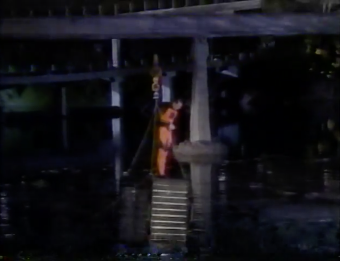 Man escapes from the submerged cage and stands onto of it.