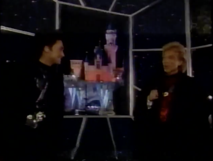 Sigfried and Roy stand in front of a black portal that shows a view of Sleeping Beauty Castle. They swear there will be no camera tricks which means there will 100% be camera tricks.