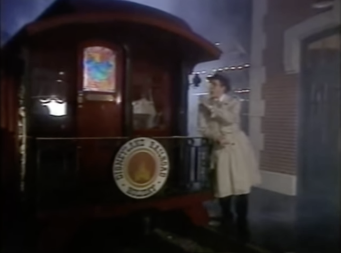 Harry Anderson stands at the back of the Disneyland train parlor car at night.