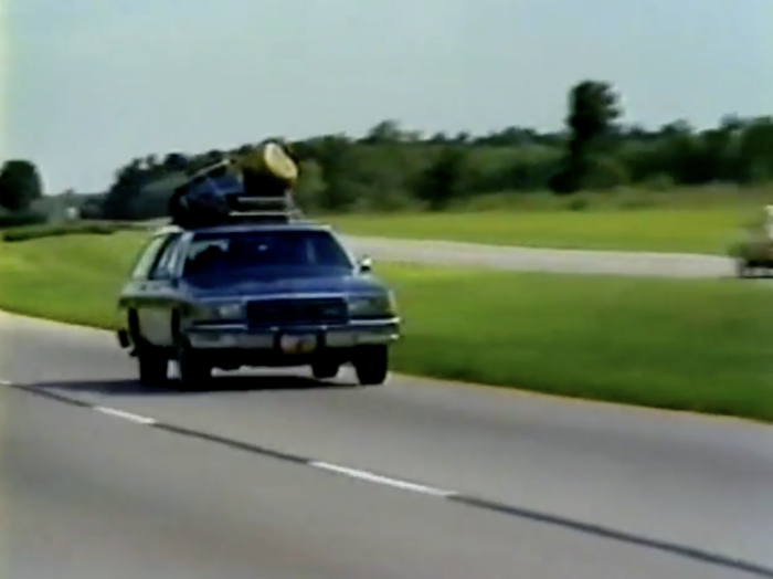 A 1970s style family wagon with suitcases precariously placed on top barreling down a Florida highway.