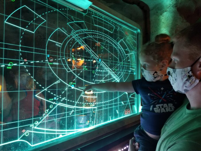 """A dad holding his daughter, who is pointing to one of the """"maps"""" in the Rise of the Resistance queue"""