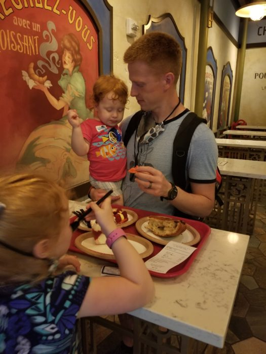 A dad and two daughters eating pastries in Les Halles at EPCOT