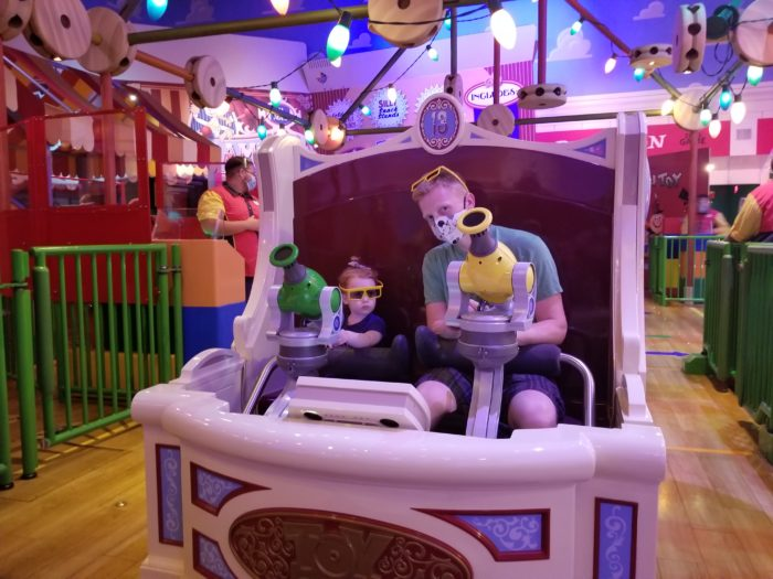 A dad and his daughter on the Toy Story Mania ride vehcile