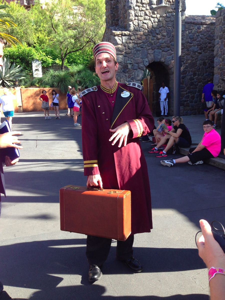 A bellhop carries a suitcase