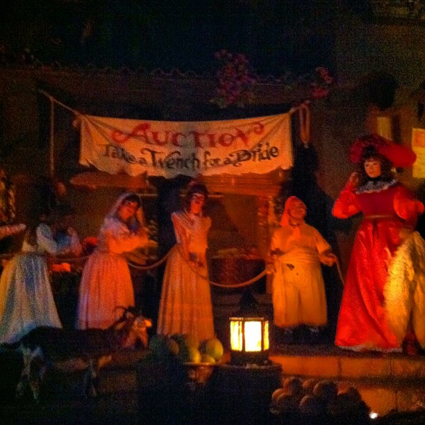 A line of women in front of a sign that says Auction: Take a Wench for a Bride from the Pirates of the Caribbean attraction