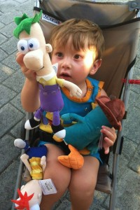 a toddler at epcot looks at Phineas and Ferb plush toys