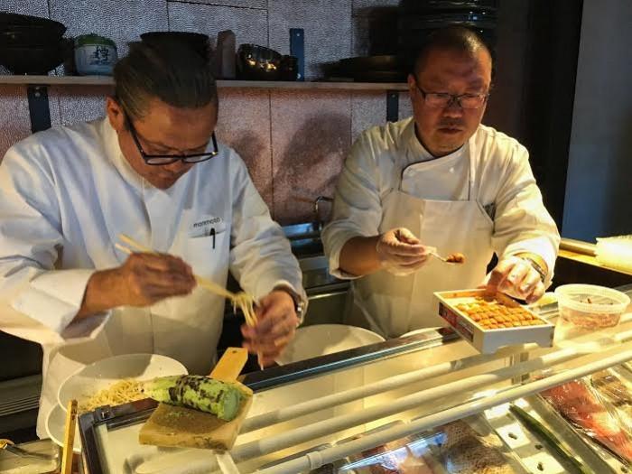 Chefs prepare the lo mein and uni for the carbonara dish