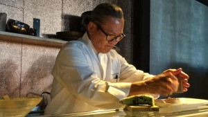 Chef Morimoto grating sea salt on a piece of octopus nigiri